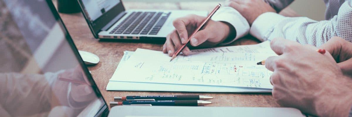 Zwei Personen, die zusammen an einer Lösung auf einem Blatt Papier arbeiten