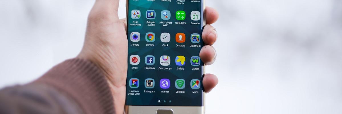 App-Menü eines Handys, das in einer Hand gehalten wird