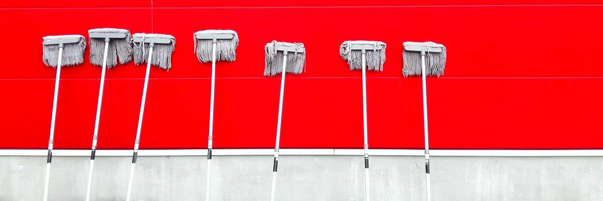 Wischmopps an eine rote Wand gelehnt